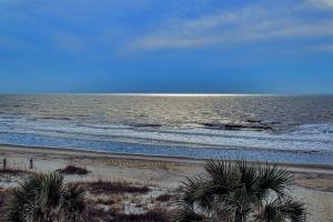 A fog bank casts sparkling light on the horizon.  Ocean Isle Beach, North Carolina.