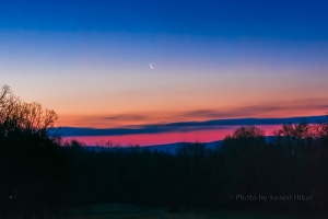 A crescent moon in the dawn sky behind our house. April 5, 2016.